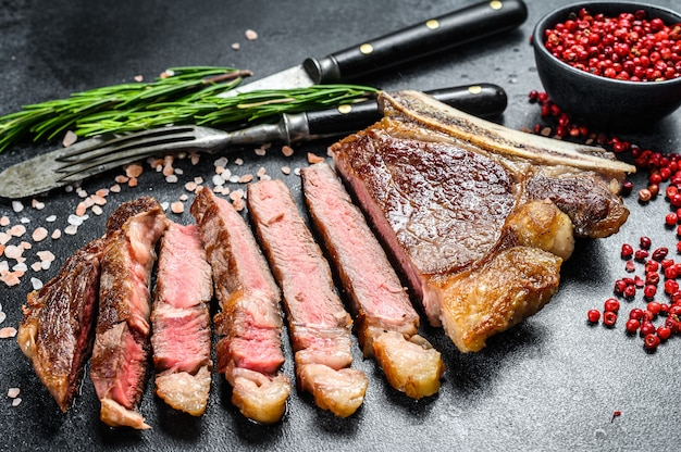 Grilled cowboy or ribeye beef steak with herbs and spices.