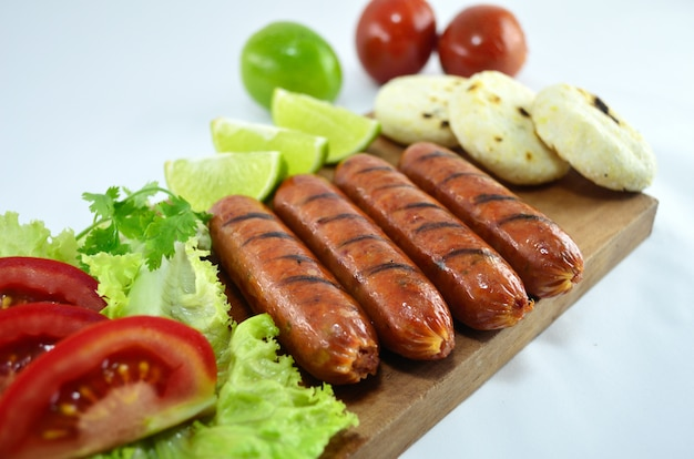 Grilled creole sausage with vegetables on wooden board.