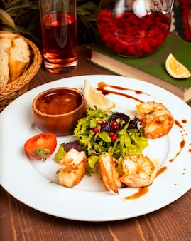 Grilled crevettes with green salad, tomatoes, lemon and dip sauce in white plate