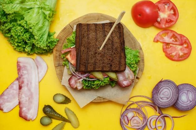 Grilled dark bread sandwich on wooden plate on yellow board