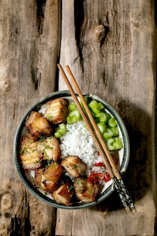 Grilled deep fried pork belly in bowl with rice, celery, chili pepper and spring onion with chopsticks over old wooden background. flat lay, copy space