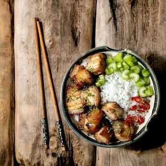 Жареный во фритюре свиной живот в миске с рисом, сельдереем, перцем чили и зеленым луком с палочками для еды на старом деревянном фоне. плоская планировка, копия пространства. квадратное изображение
