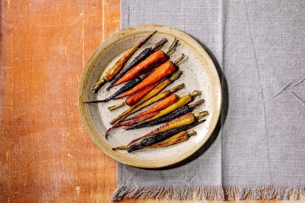Жареная морковь разного цвета на керамической тарелке с серой тканевой салфеткой на оранжевой каменной поверхности. вид сверху, плоская планировка. скопируйте пространство. веганский ужин