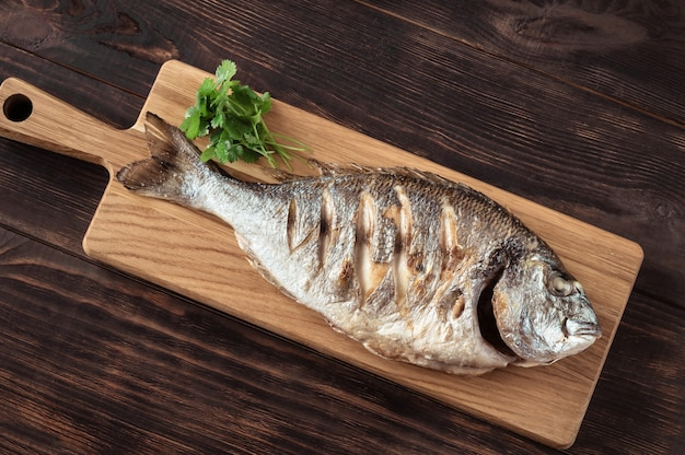 Grilled dorada fish on the wooden board