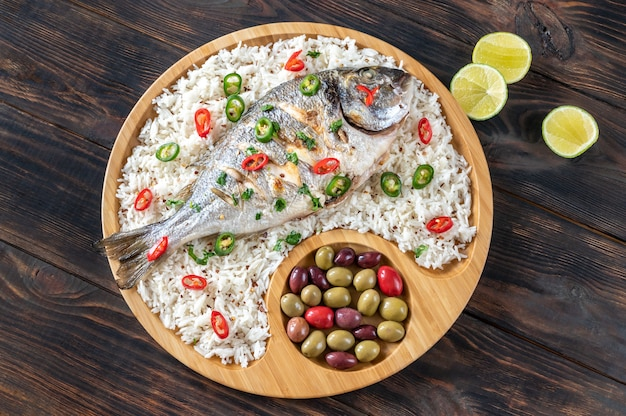 Grilled dorada garnished with white rice and marinated olives