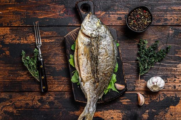 Жареная рыба морского леща дорада на разделочной доске. темный деревянный фон. вид сверху.