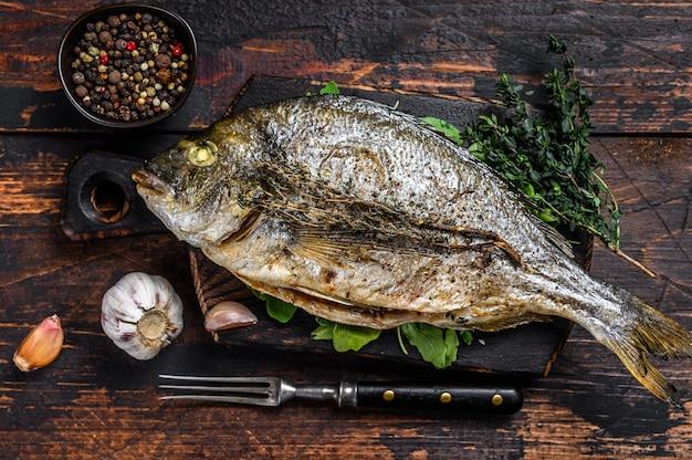 Жареная рыба морского леща дорада на разделочной доске