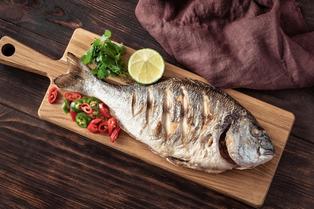 Grilled dorada with chili pepper, fresh cilantro and lime on the wooden board