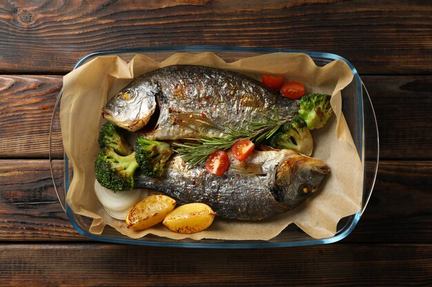 Grilled dorado in baking tray on wooden background, top view