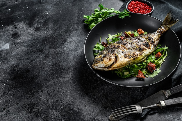 Grilled dorado fish with arugula salad and tomatoes. black background. top view. copy space