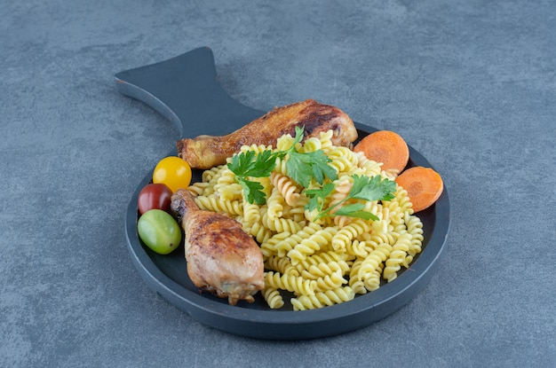 Grilled drumsticks and fusilli pasta on wooden board.