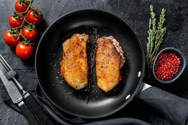Жареное филе утиной грудки на сковороде. вид сверху