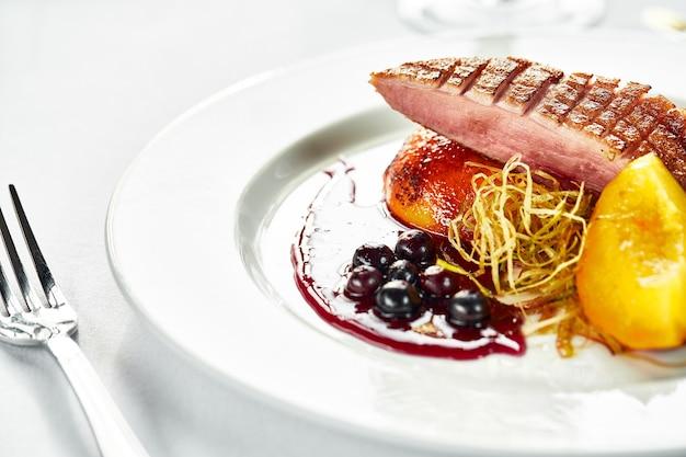 베리 소스에 복숭아를 곁들인 구운 오리 가슴살, 디저트 장식이 있는 오리 고기 클로즈업, 스베후 전망, 밝은 배경.