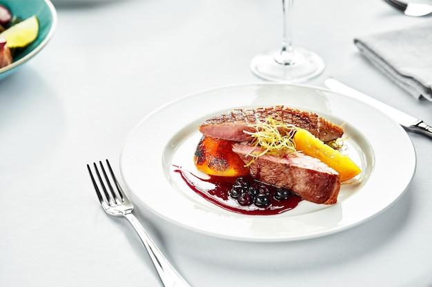 베리 소스에 복숭아를 곁들인 구운 오리 가슴살, 하얀 접시에 구운 오리 필레, 결혼식 테이블에 오리 고기를 제공하는 연회.