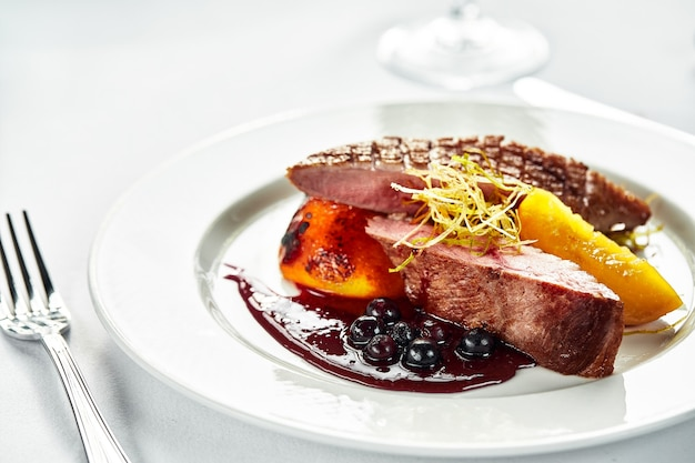 鴨胸肉のベリーソース焼き、白いプレートに鴨の切り身のグリル、鴨肉のデザートガーニッシュのクローズアップ。