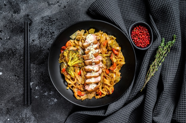 Grilled duck breast with udon noodles and vegetables. black background. top view