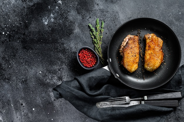 Grilled duck breasts in a pan. black background. top view. copy space