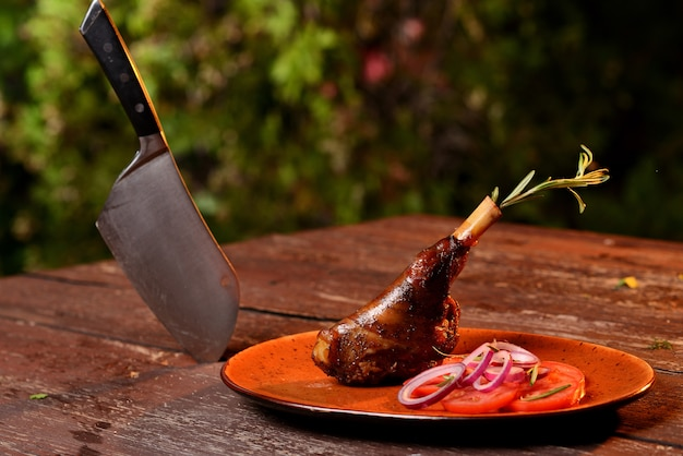 Grilled duck leg with vegetables. in a red plate on a wooden table