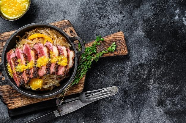 鴨肉の胸肉フィレステーキのグリル、麺とみかんソース添え。黒の背景。上面図。スペースをコピーします。