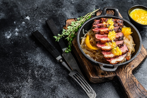Grilled duck meat breast fillet steak with noodles and tangerines sauce.