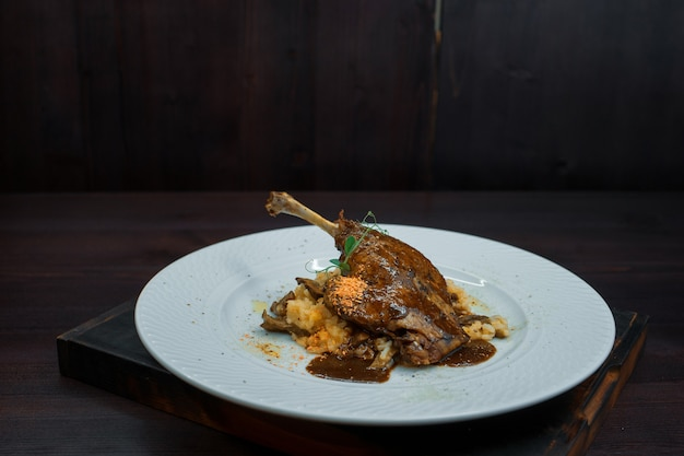 카페에서 하얀 접시에 와인 소스에 죽과 구운 된 오리. 뜨거운 맛있는 점심.