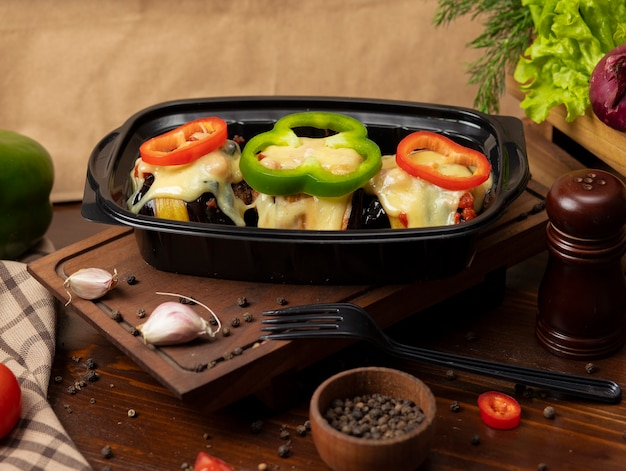 Grilled eggplant slices stuffed with meat and melted cheese on the top with bell pepper slices takeaway