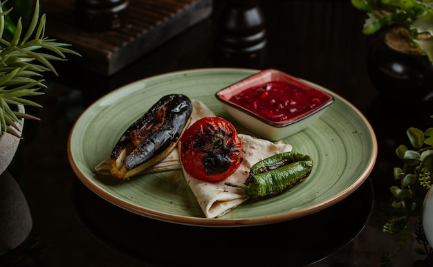 Grilled eggplant tomato and green pepper with chili sauce.