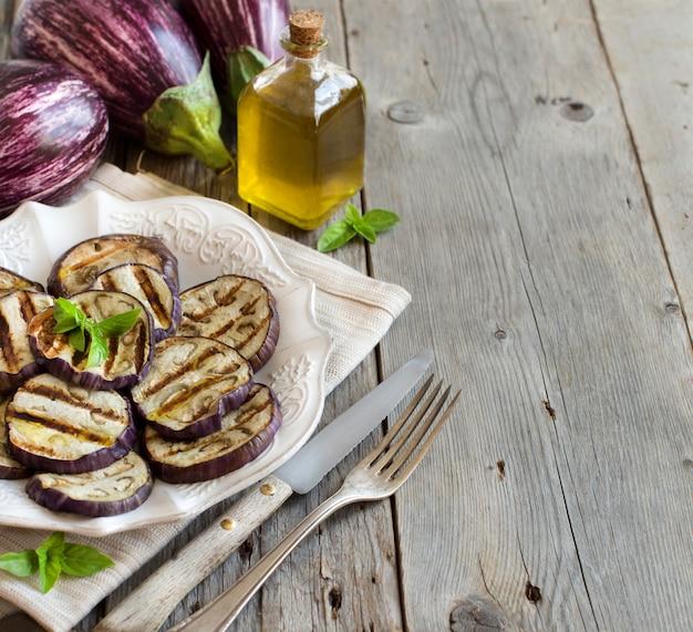 木製のテーブルにオリーブオイルで味付けした焼きナスのクローズアップコピースペース