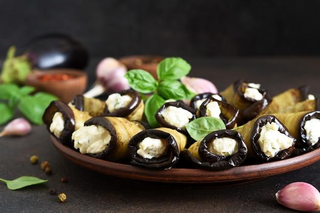 Жареные баклажаны с сыром, орехами и чесноком на фоне бетона.