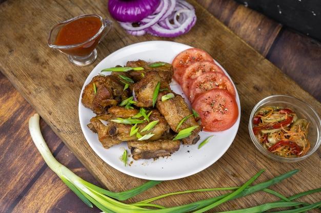 骨付きの脂肪ポークリブのグリルを野菜と一緒に皿に盛り付けます。