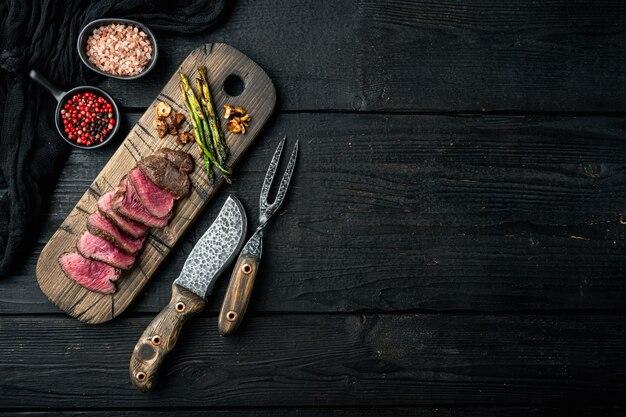 구운 등심 쇠고기 스테이크 세트, 양파와 아스파라거스, 나무 서빙 보드, 고기 나이프와 포크, 검은 나무 테이블, 평면도 평면 누워