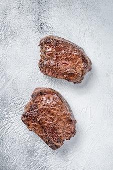 キッチンテーブルで焼いたフィレミニョンまたはテンダーロインビーフステーキ。白色の背景。上面図。