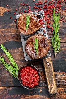 Стейк из филе миньон, приготовленный на мясорубке. темный деревянный фон. вид сверху.