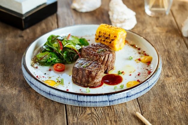 Grilled fillet mignon steaks with corn and salad