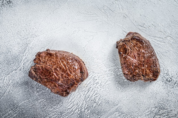 Grilled fillet mignon or tenderloin beef steak on kitchen table. white background. top view.