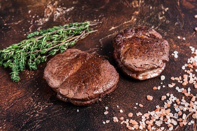フィレミニョンのテンダーロインミートビーフステーキのグリル。暗い背景。上面図。