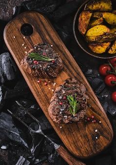 木製のまな板でグリルしたフィレステーキ。ジューシーでジューシーなグリルステーキのジューシーな部分に、古い木の板にトマトとローストポテトを添えました。上面図。