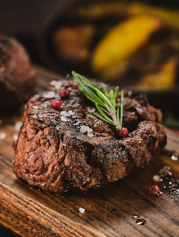 Grilled fillet steaks on wooden cutting board. succulent thick juicy portions of grilled fillet steak served with roast potatoes on an old wooden board.
