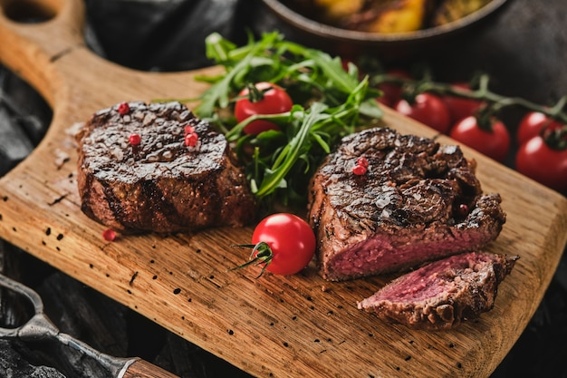 Grilled fillet steaks on wooden cutting board succulent thick juicy portions of grilled fillet steak
