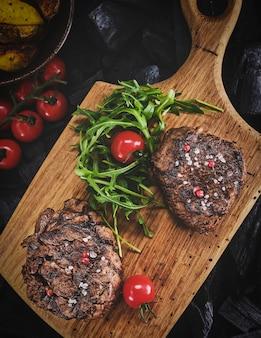 Grilled fillet steaks on wooden cutting board