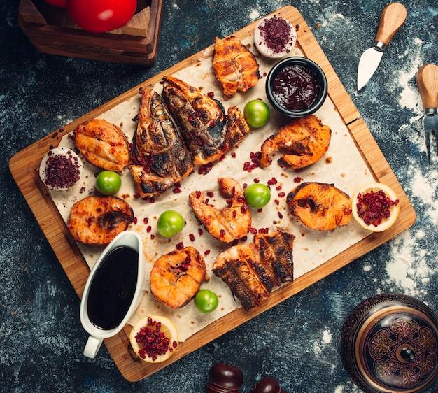 Рыба на гриле, нарезанная на кусочки, подается на лепешке с соусами, сумах