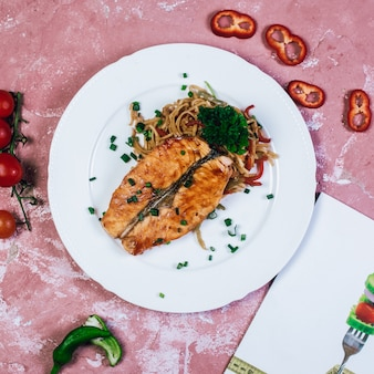 Grilled fish fillet with herbs and vegetable salad. top view.