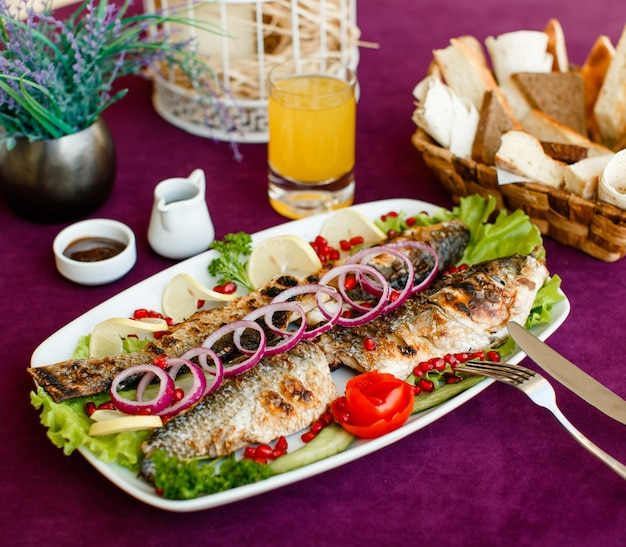 Grilled fish garnished with red onion, tomato, lettuce, lemon and pomegranate