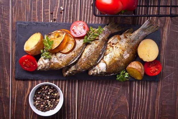 Жареная рыба на тарелке с лимоном и овощами.