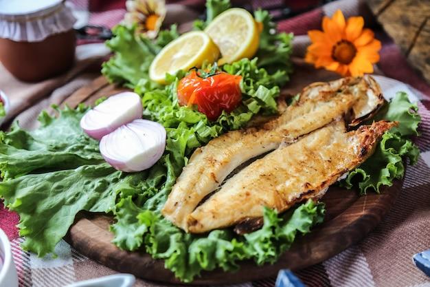 Рыба гриль на деревянной доске лук салат помидор лимон