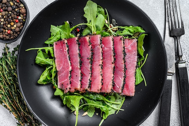 ルッコラのサラダを添えた魚のマグロステーキスライスのグリル。白色の背景。上面図。
