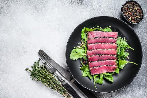 Кусочки стейка из тунца на гриле в тарелке с салатом из рукколы