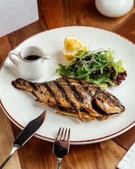Жареная рыба парик зеленый салат и гранатовый соус вид сбоку