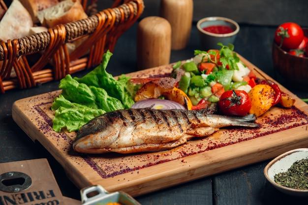 Рыба на гриле с салатом из свежих овощей, листьями салата и сумах