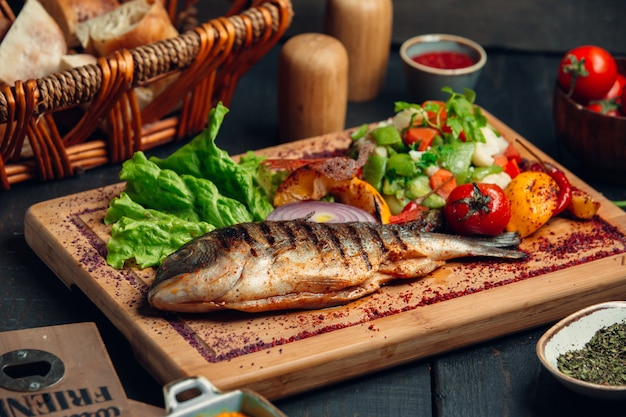 Grilled fish with fresh vegetable salad, lettuce and sumac sprinkles